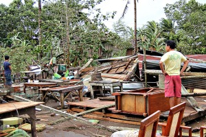 A man looks at his damaged house destroyed by strong winds brought about by Typhoon Bopha in Butuan City, Agusan del Sur, in southern island of Mindanao on December 4, 2012. (AFP Photo/Erwin Mascarinas)