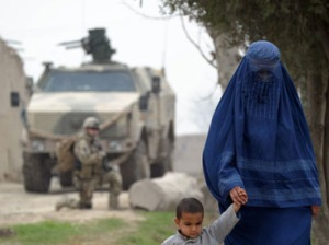An Afghan woman and her child walk past German soldiers on patrol in Nahr-i Sufi near the DHQ.(AFP Photo / Johannes Eisele)