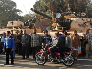 Supporters of the Muslim Brotherhood stand near tanks that were just deployed outside the Egyptian presidential palace in Cairo December 6, 2012. (Reuters/Asmaa Waguih)
