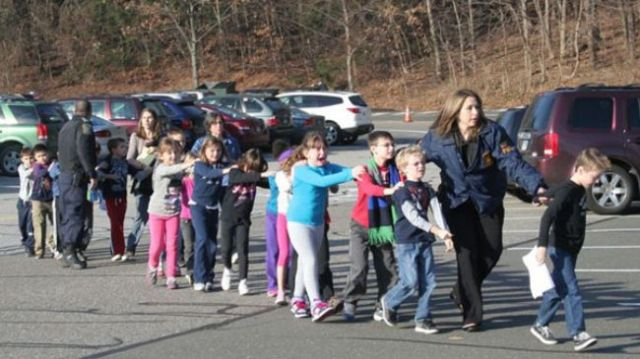 Students are escorted from Sandy Hook Elementary School after a shooting spree on December 14, 2012.