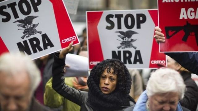 Hundreds of protesters swarmed the Washington office of the National Rifle Association on Monday to deplore the powerful pro-gun lobby group and push for tougher gun control laws in reaction to recent killing of 27 in Newtown, Connecticut.
