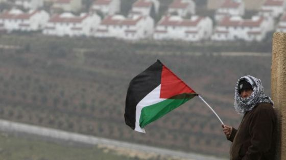 A Palestinian man waves his national flag to protest against the expansion of illegal Israeli settlements. (file photo)
