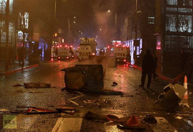 Burning debris is seen on the lower Newtownards road as police landrovers and a watercanon confront Loyalist protesters gather at Belfast City Hall during a city council meeting in Belfast, Northern Ireland on January 7, 2013. (AFP Photo/Peter Muhly)