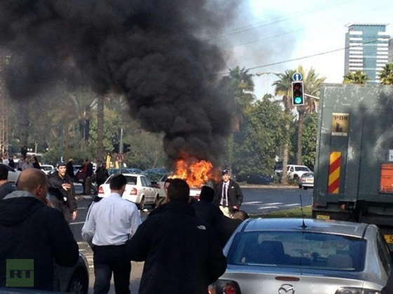 Investigators look at a damaged car after it exploded near the Israeli defence ministry injuring several people in Tel Aviv on January 10, 2013. (AFP Photo / Roni Schutzer)