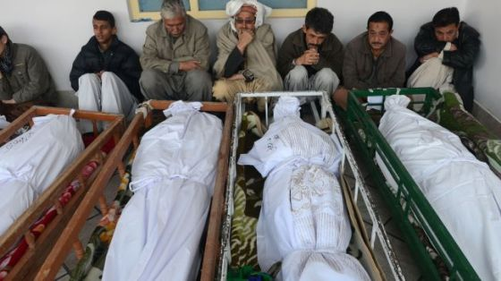 Pakistani Shia Muslim mourners sit beside the coffins of bombing victims at a mosque in Quetta, Balochistan Province, January 11, 2013.
