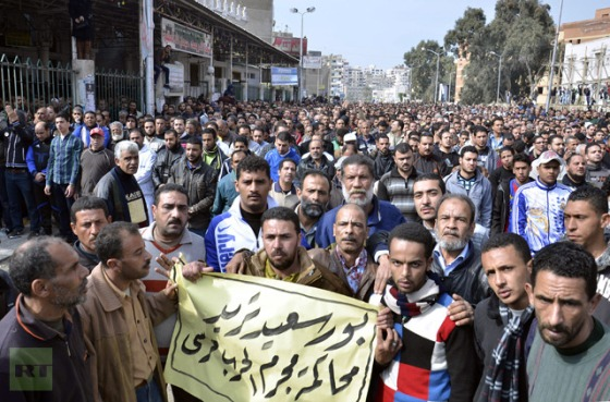 "Egyptian mourners carry a placard reading in Arabic ""Port Said wants to trial the war criminal Morsi'"" as they march in the canal city of Port Said on January 28, 2013 (AFP Photo / Str)"