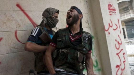 Syrian militants take cover as they exchange fire with government forces in the northern city of Aleppo. (file photo)