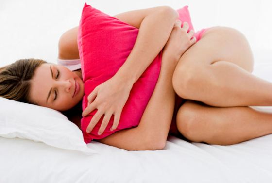 Woman curled up in fetal position, hugging a pillow.
