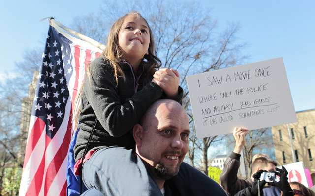 Nine year old Summer Stayton sits on her dad Jason Stayton's shoulders as they listens to speakers during the Guns Across America pro-gun rally at the State Capitol in Atlanta, Georgia, January 19, 2013. (Reuters / Tami Chappell)
