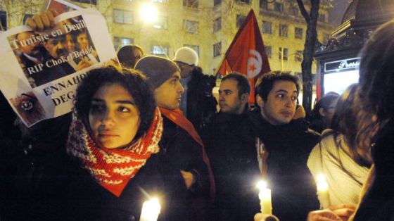 A protester holds a poster as others hold candles during a demonstration outside the Tunisian Embassy in Paris on February 6, 2013, against the killing of prominent Tunisian opposition leader Shokri Belaid.
