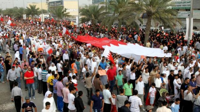File photo shows Bahraini protesters carrying their national flag during an anti-regime demonstration in the capital, Manama.