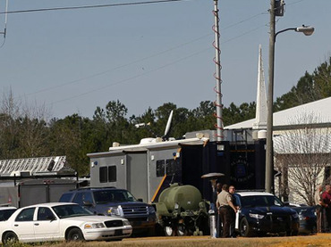 Law enforcement officials near the scene of a shooting and hostage taking near Midland City. (Reuters / Philip Sears)
