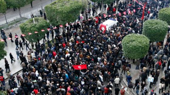 The body of Tunisian opposition Shokri Belaid (top R) arrives amidst tens of thousands of protesters as they demonstrate on Avenue Habib Bourguiba in Tunis February 6, 2013.