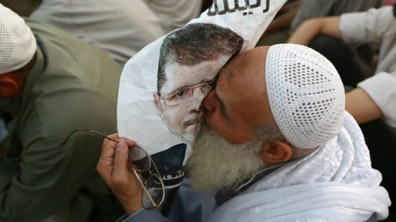 An Egyptian man, supporter of the Muslim Brotherhood and Egypt's ousted president Mohamed Morsi kisses a poster of him as worshipers gather for a dusk payer outside Cairo's Rabaa al-Adawiya mosque on July 11, 2013.(AFP Photo / Marwan Naamani)