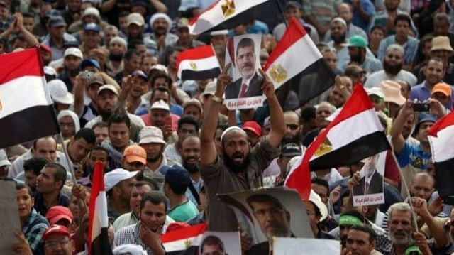 Supporters of ousted Egyptian President Mohamed Morsi hold portraits of him during a demonstration in Cairo. (File photo)