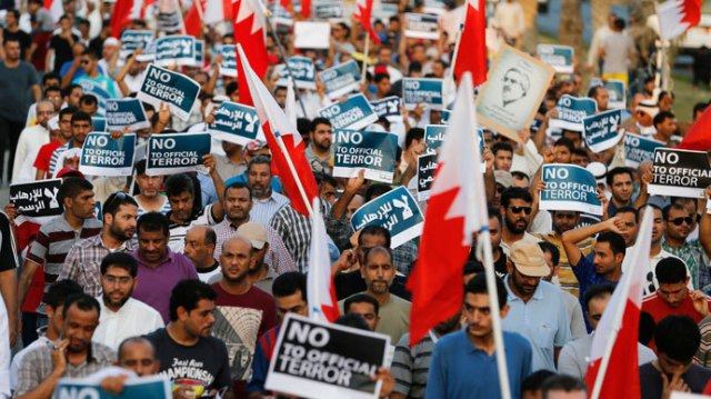 "Anti-government protesters holding Bahraini flags and signs saying ""No To Official Terror"" march during a rally organized by Bahrain's main opposition party Al Wefaq on Budaiya highway west of Manama, August 23, 3013.(Reuters / Hamad I Mohammed)"