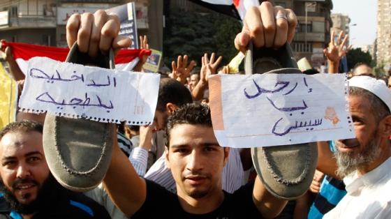A supporter of Muslim Brotherhood and ousted Egyptian President Mohamed Morsi shows his shoes with notes written on them during a protest in Cairo August 23, 2013 (Reuters / Muhammad Hamed)
