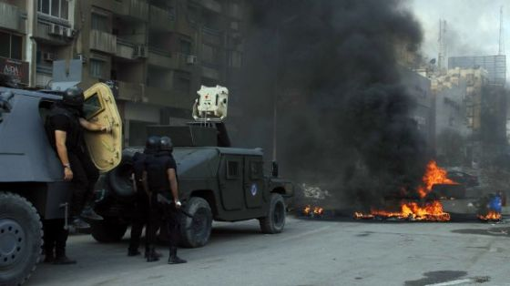 Egyptian security forces stand guard in front of a blaze in Cairo, August 14, 2013.