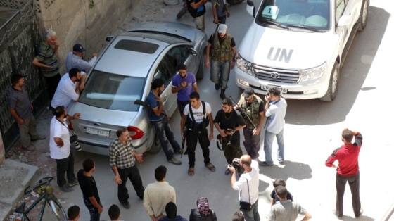 Opposition fighters, civilians and journalists stand near a United Nations (UN) vehicle as UN arms experts inspect the site where rockets had fallen in Damascus' eastern Ghouta suburb on August 28, 2013 (AFP Photo / Mohamed Abdullah)