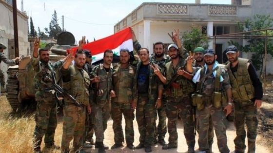 Syrian army soldiers pose for a photograph as they hold the Syrian national flag in the village of Debaa near Qusair (file photo).