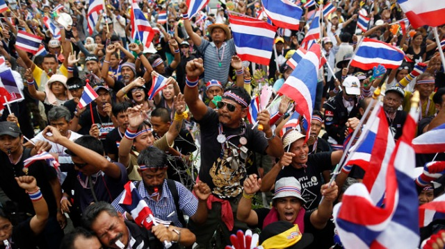 Anti-government protesters wave flags and blow whistles as one of their leaders addresses them at the Finance Ministry, which they have occupied since Monday, in Bangkok November 26, 2013. (Reuters/Damir Sagolj)