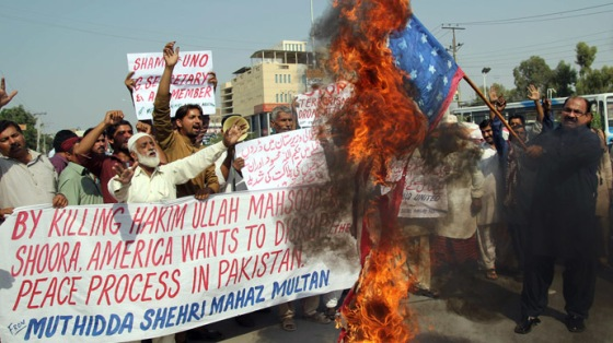A Pakistani protester from United Citizen Action (UCA) holds a burning US flag as others shout anti-US slogans during a protest against the killing of Taliban leader Hakimullah Mehsud in a US drone attack in Pakistani tribal region, in Multan on November 2, 2013. (AFP Photo/S. S. Mirza)